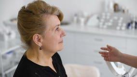 Доктор дает диагноз портрет усмехаясь старшей женщины в офисе доктора сток-видео
