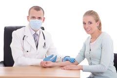 Доктор беря пробу крови от молодого женского пациента Стоковое Фото