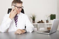 Доктор беседуя на его мобильном телефоне стоковое изображение rf