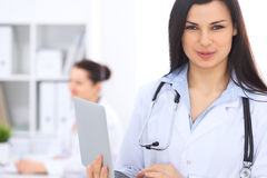 Доктор брюнет женский на предпосылке коллег говоря друг к другу в больнице Врач готов помочь Стоковое фото RF