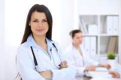 Доктор брюнет женский на предпосылке коллег говоря друг к другу в больнице Стоковые Фотографии RF