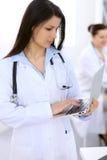 Доктор брюнет женский на предпосылке коллег говоря друг к другу в больнице Стоковое Фото