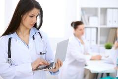 Доктор брюнет женский на предпосылке коллег говоря друг к другу в больнице Стоковые Изображения RF
