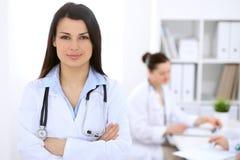 Доктор брюнет женский на предпосылке коллег говоря друг к другу в больнице Стоковое фото RF