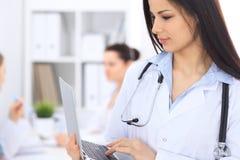 Доктор брюнет женский на предпосылке коллег говоря друг к другу в больнице Врач готов помочь Стоковые Фотографии RF