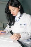 Доктор брюнет пишет анамнез после консультации Стоковое Фото