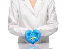 Доктор в белой мантии и перчатки держа таблетки и капсулы Стоковая Фотография