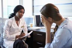 Доктор в консультации c подавленным женским пациентом Стоковое фото RF