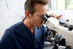Доктор в образцах лаборатории проверяя через микроскоп стоковое фото rf