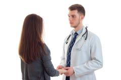 Доктор в форме держит его терпеливую руку ` s и смотреть ее Стоковые Фото