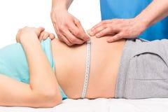 Доктор гинеколога измеряет том брюшка стоковые фото
