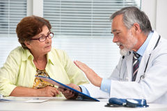 Доктор говоря к его женскому пациенту стоковые фотографии rf