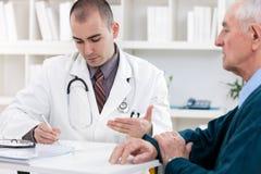 Доктор говоря к старшему пациенту Стоковое Фото
