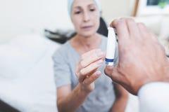 Доктор дает женщине пилюльку Женщина проходит реабилитацию после лечения рака Стоковое фото RF