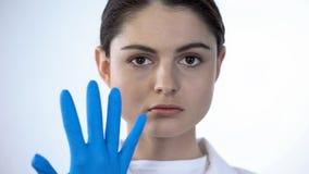 Доктор дамы кладя на хирургические перчатки, подготавливая рассмотреть пациента, медицины стоковые изображения