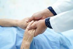 Доктор держа касаться старшему рук азиатскому или пожилому пациенту женщины пожилой женщины с любовью, заботой стоковое изображение rf