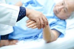 Доктор держа касаться старшему рук азиатскому или пожилому пациенту женщины пожилой женщины с любовью, заботой, помогая, ободряет стоковая фотография