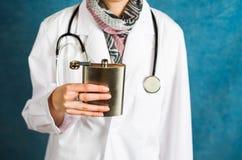 Доктор держа тазобедренный конец склянки вверх стоковая фотография