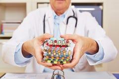 Доктор держа много пилюлек внутри в руках стоковые изображения rf