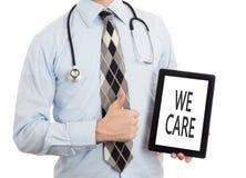 Доктор держа таблетку - мы заботим Стоковые Изображения RF