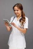 Доктор женщины в белой медицинской форме с таблеткой в руке Стоковое Изображение RF