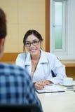 Доктор женщины говоря к ее мужскому пациенту на офисе Стоковые Изображения RF