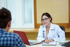 Доктор женщины говоря к ее мужскому пациенту на офисе Стоковое Изображение