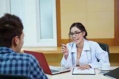 Доктор женщины говоря к ее мужскому пациенту на офисе Стоковое Изображение RF