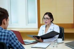Доктор женщины говоря к ее мужскому пациенту на офисе Стоковые Изображения