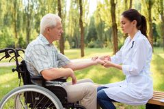 Доктор женщины измеряет ИМП ульс пожилого пациента на кресло-коляске Стоковые Изображения