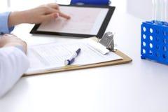 Доктор женщины используя планшет пока сидящ на столе в крупном плане больницы Кардиолог проверяет диаграммы сердца стоковые изображения