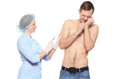 Доктор женщины кладет укол Человек испуган и Стоковое Изображение RF
