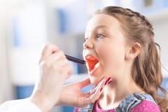 Доктор женщины проверяя горло маленькой девочки Стоковая Фотография