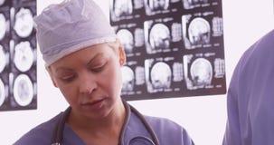 Доктор женщины рассматривая рентгеновские снимки с коллегой Стоковое Изображение RF