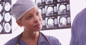 Доктор женщины рассматривая рентгеновские снимки с коллегой Стоковые Изображения