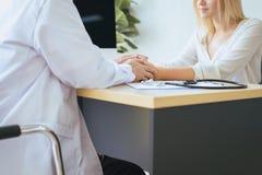 Доктор женщины рук успокаивая ее женский пациента в палате, докторе давая консультацию и поощрение пациенту стоковое фото rf
