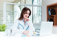 Доктор женщины сидя на таблице Стоковые Изображения