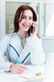 Доктор женщины сидя на таблице Стоковое Фото