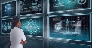 Доктор женщины смотря медицинские интерфейсы против предпосылки с пирофакелами стоковые фотографии rf