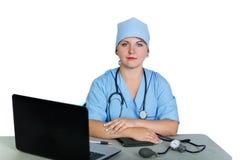 Доктор женщины со стетоскопом на таблице на белой предпосылке стоковые фото