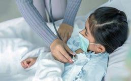 Доктор излечивает для того чтобы patien азиатский ребенк на больничной койке стоковое изображение