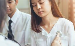 Доктор использует стетоскоп для рассмотрения пациента пациентов стоковое изображение