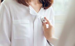Доктор использует стетоскоп для рассмотрения пациента пациентов Услышать тариф сердца стоковое фото rf