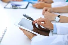 Доктор используя планшет на медицинской встрече, крупный план Группа в составе коллеги на предпосылке Стоковое Изображение RF