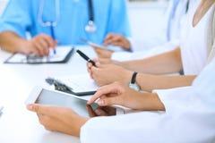 Доктор используя планшет на медицинской встрече, крупный план Группа в составе коллеги на предпосылке Стоковые Фото