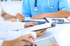 Доктор используя планшет на медицинской встрече, крупный план Группа в составе коллеги на предпосылке Стоковая Фотография RF