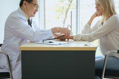 Доктор используя стетоскоп к пациенту женщины для слушая тарифа сердца на sickbed на больнице, руке выборочного фокуса стоковая фотография rf