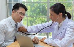 Доктор используя стетоскоп слушает к биению сердца пациента человека стоковое изображение rf