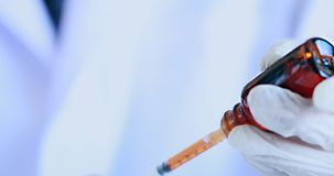 Доктор используя шприц для того чтобы высосать вакцину от бутылки акции видеоматериалы
