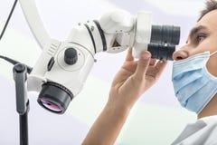 Доктор используя зубоврачебный микроскоп стоковое фото